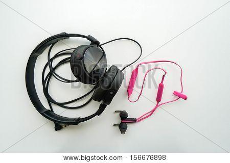 isolated black earphones for computer and pink wireless earphones