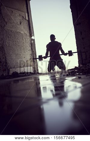 Muscular athletic built young athlete lifting weights in a ruin building next to a puddle of water
