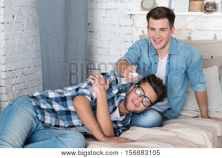 Delightful relaxation together. Two handsome young gay partners smiling and taking a photo of themselves while relaxing together on the bed.