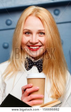 Beautiful ginger girl in white shirt with bow tie holds coffee in hands close-up on blue background