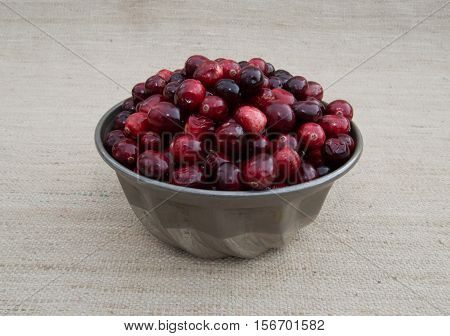 Fresh red and maroon cranberries heaped in a vintage, ridged tin bowl or food mold. Photographed close up against an ecru woven cloth background with shallow depth of field and fill flash.