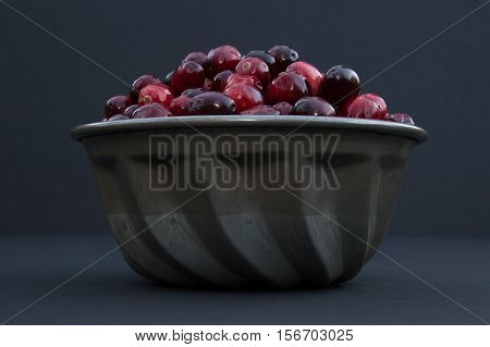 Fresh red and maroon cranberries heaped in a vintage, ridged tin bowl or food mold. Photographed close up at eye level against a black background with shallow depth of field and fill flash.