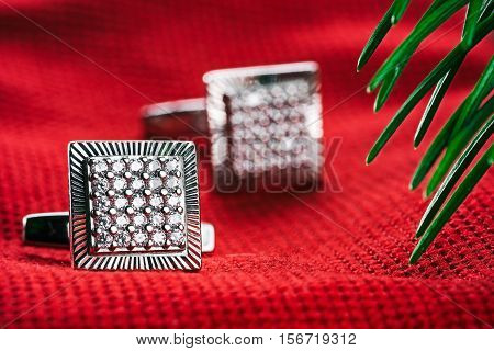 Silver square cufflinks on red textured fabric under evergreen branch. Macro detail view