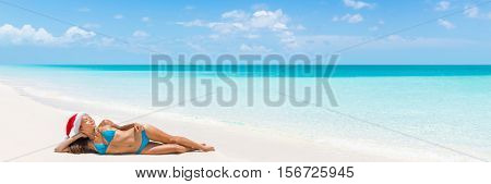 Christmas vacation beach woman banner panorama. Wide paradise beach background with Asian bikini woman lying down relaxing on white sand beach with christmas santa hat.
