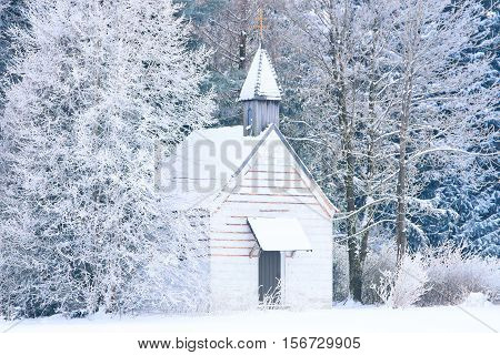 Small woody chapel in frozen snowy forest. Stock photo captured in Bavarian Alpine rural region Allgaeu.