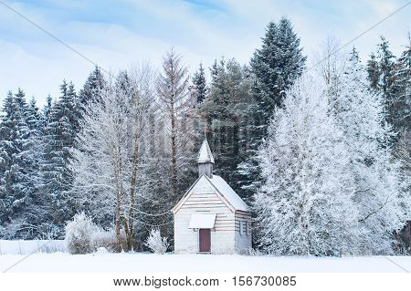 Small wooden chapel on snowbound frosty glade in snowy frozen forest. Winter wonderful scenery in German Bavarian region Allgaeu at the foot of Alps.