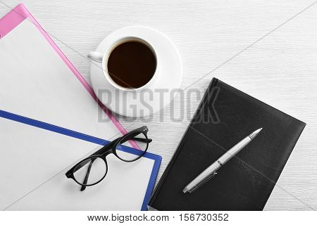Glasses, clipboards, notebook and cup of coffee on wooden table. Healthy eyes concept