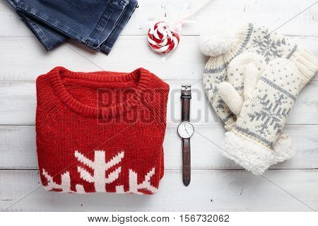 Christmas clothing style set with winter knitted sweater, jeans, cap, mittens, watches and lollipop.