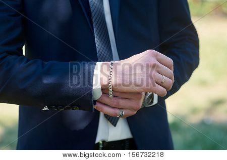 groom dress cufflinks on shirt outdoor in wedding day