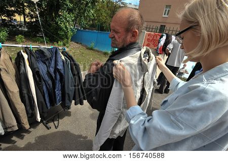 Saint-Petersburg Russia - June 23 2016: Young woman representative of a charitable organization helping the homeless to pick up clothes which they get for free.