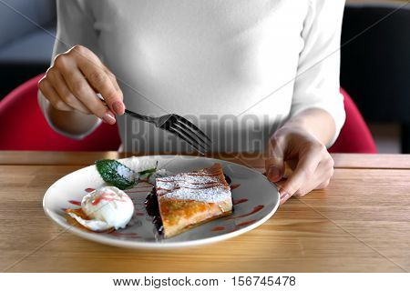 Young woman eating delicious dessert at restaurant