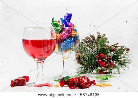 Christmas Party Treats Of Wine And Wrapped Chocolate Candy Sweets.