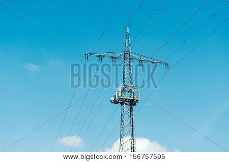 Electrical tower current mast against blue clear sky with - advertising image for environmentally friendly energy producers