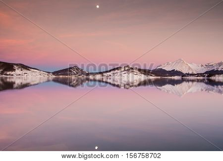 Romantic sunset with moon on the Campotosto lake in Abruzzo