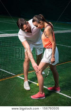 Bend it a little. Positive bearded professional tennis instructor bending leg of young woman and showing how to stand while teaching her to pley tennis