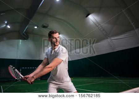 Train your skills. Pleasant profesional concentrated man holding racket and playing tennis while training in indoor tennis court
