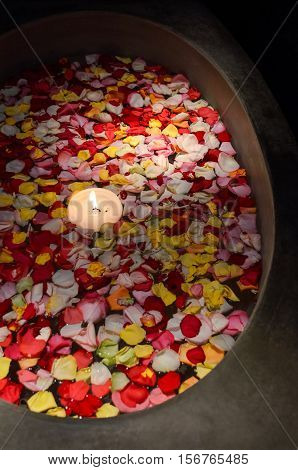 Bath with floating rose petals and candle in dark room
