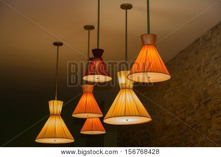 Great amzing closeup view of cones shaped vintage retro style electrical ceiling lights at night