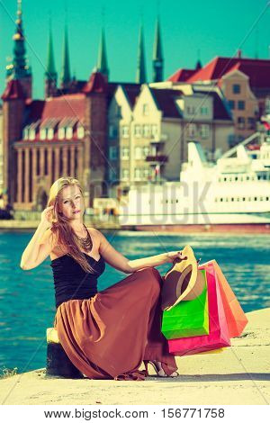Spending money buying things concept. Fashionable woman resting after big shopping sitting with bags in town wearing long dress
