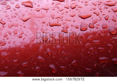 Water drops background with reflected light on the roof of a red car