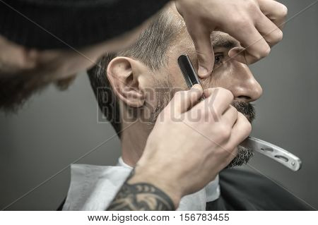 Elegance man with a beard in the barbershop. Barber with a tattoo is trimming his beard with a straight razor. Closeup. Horizontal.