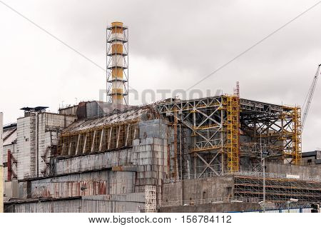 Chernobyl nuclear power plant. View on old destroyed sarcophagus before cover station of new safety confinement. Pripyat abondoned zone, Ukraine.