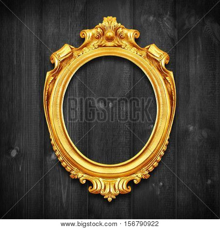 The Antique gold frame on wooden wall;. Empty Antique gold picture frame on wooden wall.