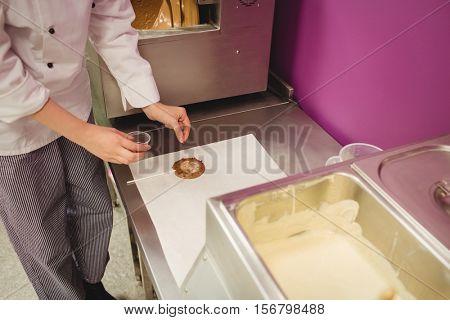 Worker preparing lollipop on wax paper in kitchen