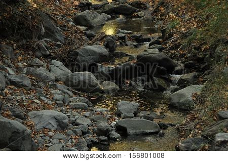 Hiking trail along the river to the waterfall Millomeris in the mountains in Cyprus
