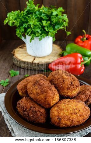 Meat mini-rolls (cutlet) with boiled egg in a clay bowl on dark wooden background.