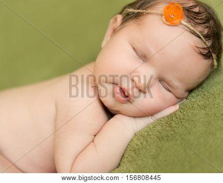 lovely newborn sleeping sweet on hand with headband, closeup