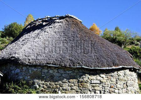 The stone house with thatched roof in the village