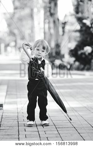 cute baby boy in a red bow tie is holding a large black umbrella. child with umbrella in hands
