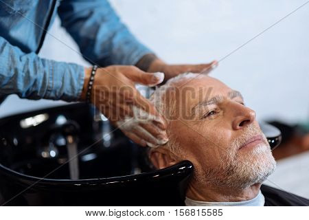 Perfect massaging. Close-up portrait of pleasant bearded man having his hair washed by hairdresser in barber shop.