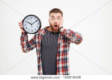 Surprised shocked young man in plaid shirt holding wall clock over white background