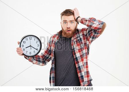 Worried bearded young man in checkered shirt holding and looking at camera over white background