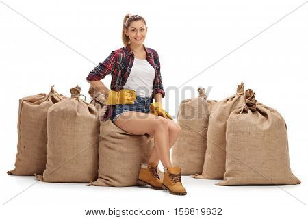 Female farmer sitting on a pile of burlap sacks isolated on white background