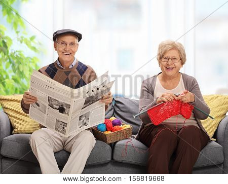 Mature man holding a newspaper and a mature woman knitting sitting on a sofa
