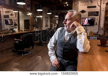 Being thoughtful. Portrait of attractive thoughtful senior man looking aside and leaning on arm while sitting at bar counter in barbershop.
