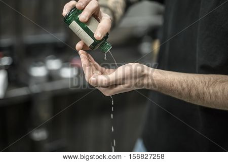 Green bottle with the lotion in the man's hands on the blurry background of the barbershop. Guy is pouring the lotion on his hand. Closeup. Horizontal.