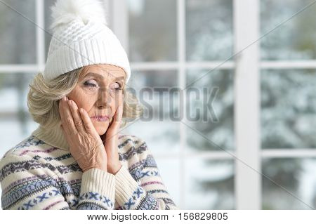 Portrait of thoughtful senior woman in hat looking at the distance  with hands on her cheeks