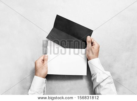 Hand holding black blank envelope and folded leaflet mockup, isolated. Arm hold empty brochure template mock up. Greeting card flyer design. Invitation printing display. Reading writing in envelope.