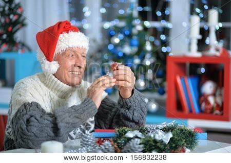 Smiling senior man with hand made Christmas decoration sitting at the table at home