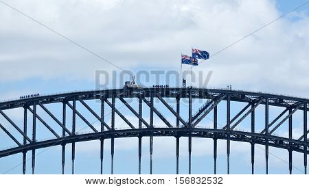 Sydney Australia - October 23 2016: The Australian National flag (R) and the state flag of New South Wales (L) flies above Sydney Harbour Bridge in Sydney Australia