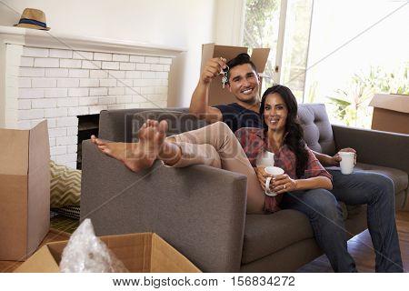 Couple On Sofa Holding Keys Taking A Break On Moving Day