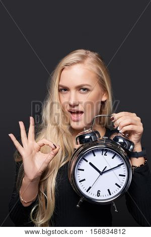 Excited woman with big alarm clock gesturing OK sign over grey background