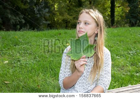 Autumn, Young Girl Who Is Holding In Hand A Leaf