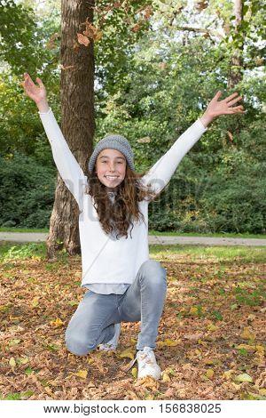 Preteen Girl Raises Hands To Sky In Hand, Autumn
