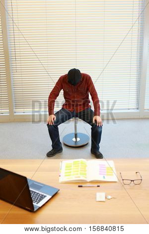anonymous male in black sack on head resting on pneumatic chair in the office - burnout syndrome