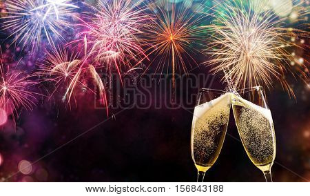 Two glasses of champagne over fireworks background. Celebration concept, free space for text
